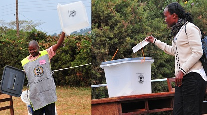 A polling assistant displays an empty box as a lady casts her vote