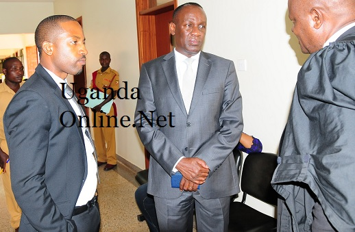 Meddie and Capt Mike Mukula listen to a lawyer at the commercial court